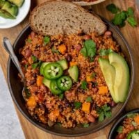 close up overhead shot of bowl of quinoa butternut squash and bean chili with avocado slices, jalapeño slices, fresh cilantro, and bread on top