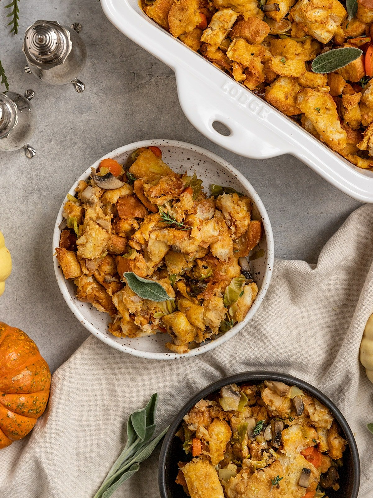 two bowls of stuffing with fresh sage and fresh thyme on top as garnish