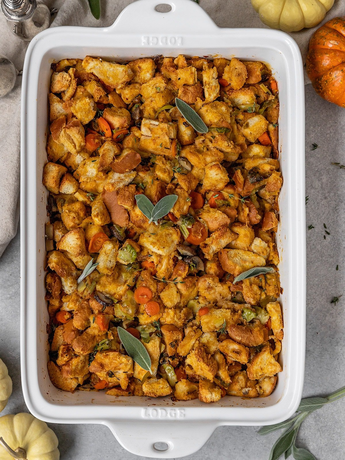 a white rectangle casserole dish filled with bread stuffing, vegetables, fresh sage, and fresh thyme