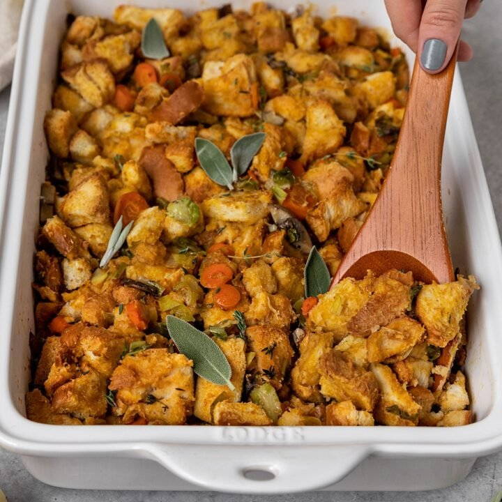 a wooden serving spoon digging into a casserole dish full of vegetable bread stuffing