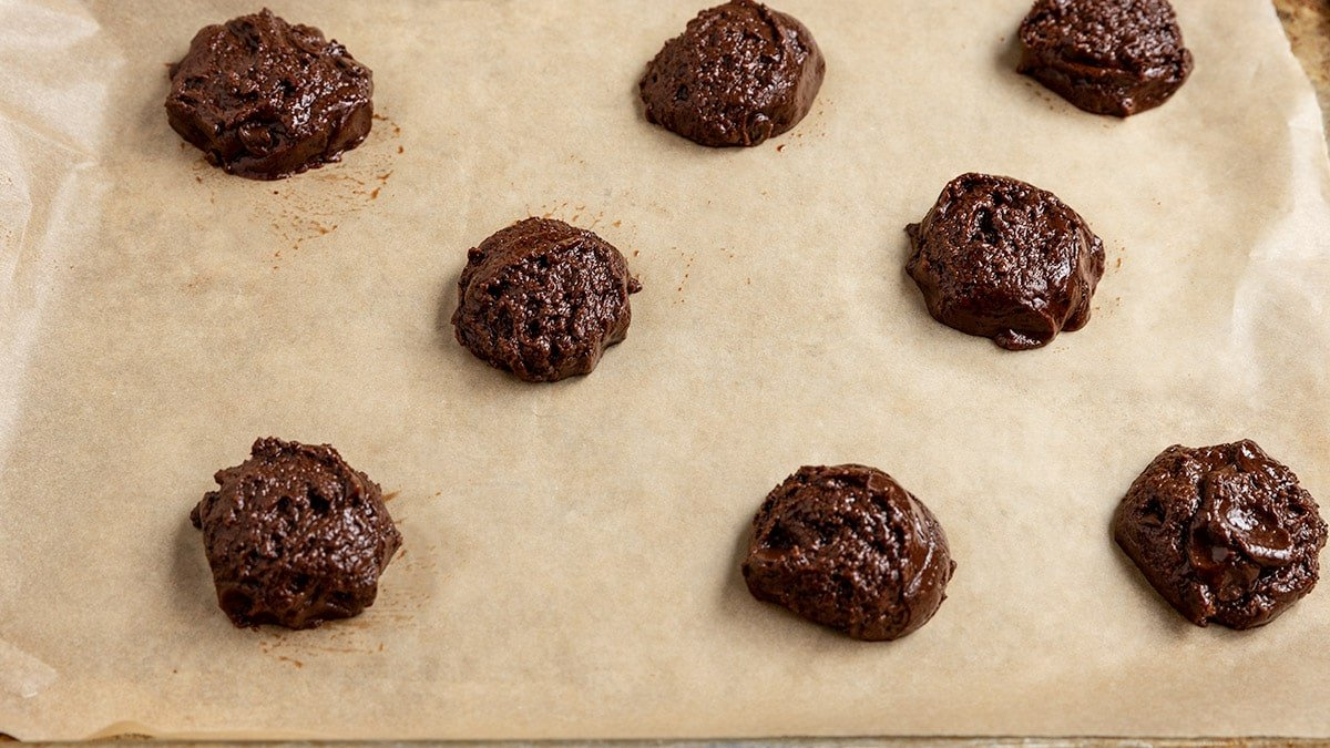 tray of scooped brownie cookie dough on parchment lined baking tray