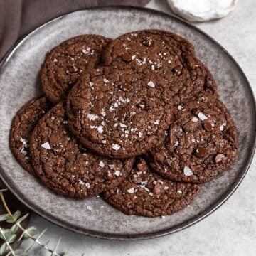 plate full of crinkled chocolate cookies with flaky sea salt on top