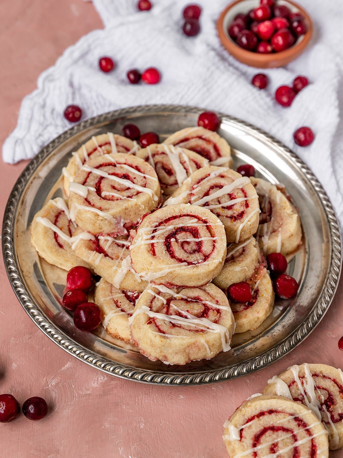 plate full of cranberry orange swirl cookies with fresh cranberries