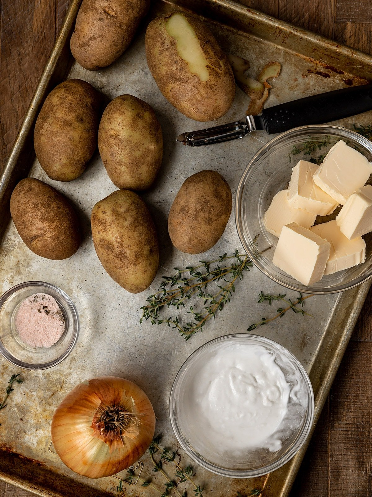 tray of ingredients including potatoes, vegan butter, coconut milk, fresh thyme, salt, pepper, and an onion