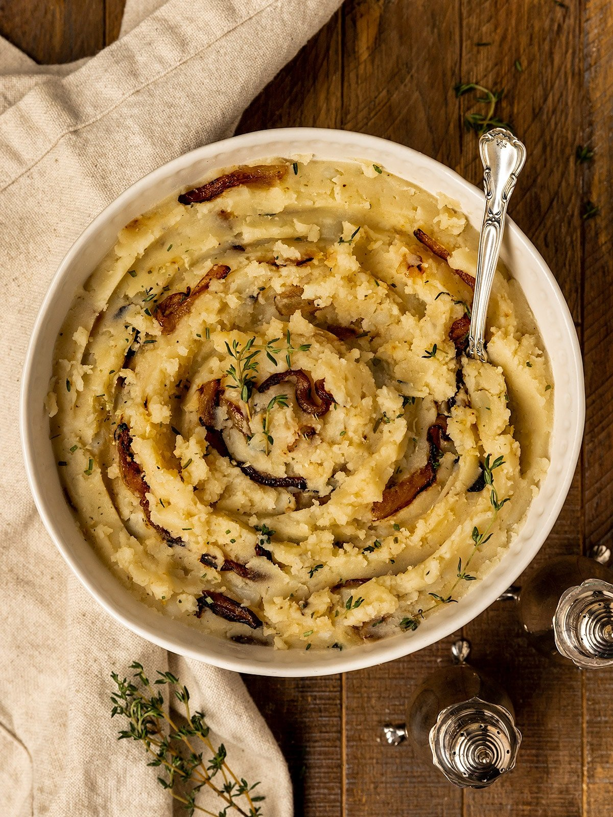 bowl containing mashed potatoes with caramelized onions and fresh thyme with side of salt & pepper shakers