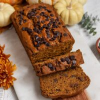 loaf of pumpkin chocolate chip bread with 2 slices cut out