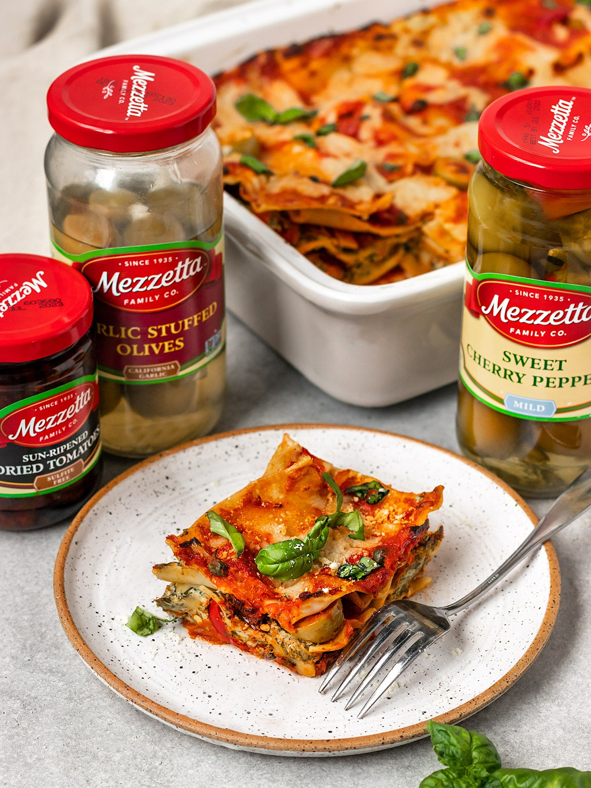 slice of lasagna on a plate surrounded by mezzetta bottles of sweet cherry peppers, sun dried tomatoes, and garlic stuffed olives