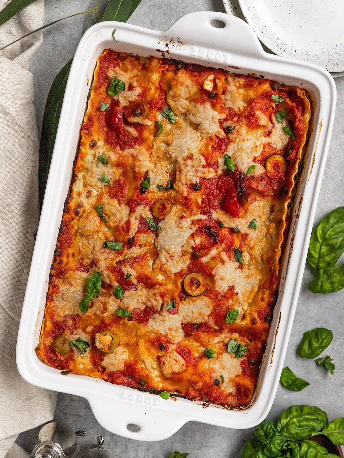 a large casserole dish filled with lasagna topped with tomato sauce, vegan cheese, and basil