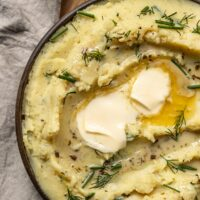 a close up shot of mashed potatoes with pools of butter, fresh dill, and fresh chives