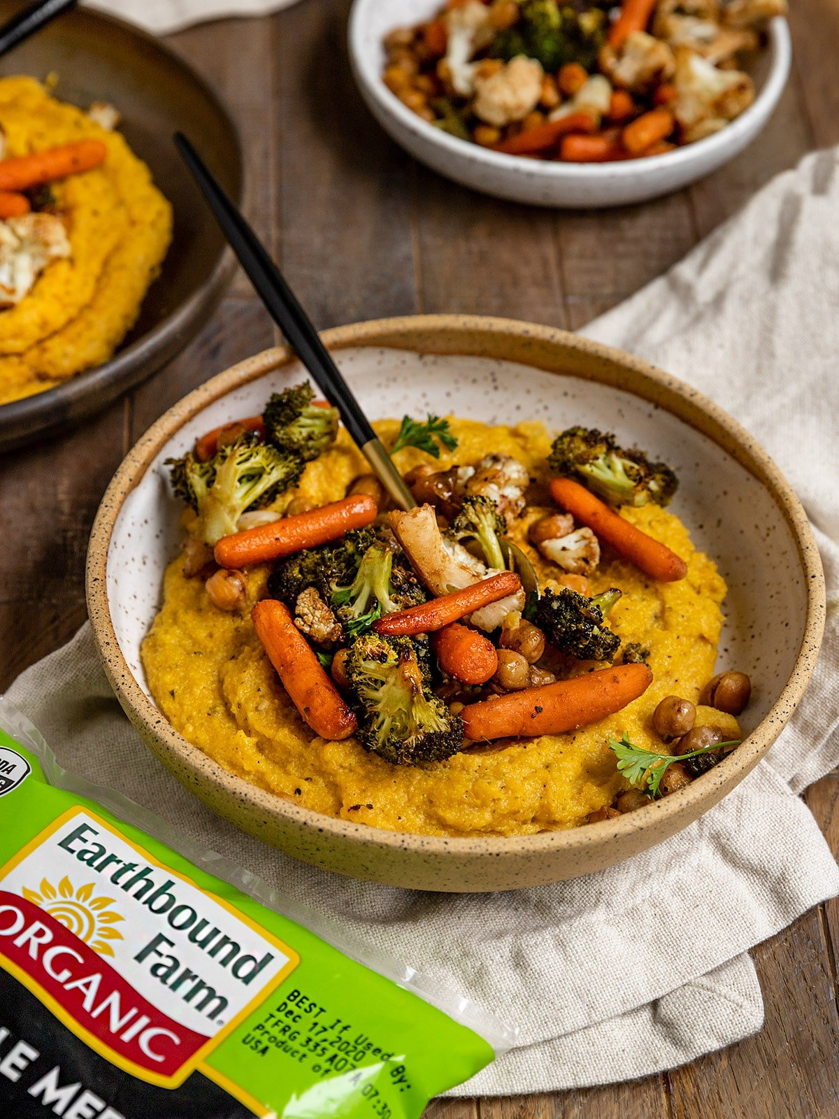 bowl of polenta with carrots, chickpeas, broccoli, cauliflower, and a spoon