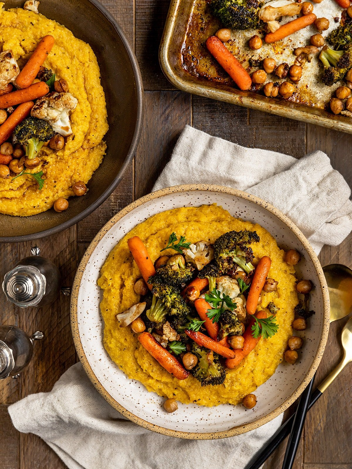 two bowls of polenta with roasted veggies on top and a tray of roasted veggies on the side