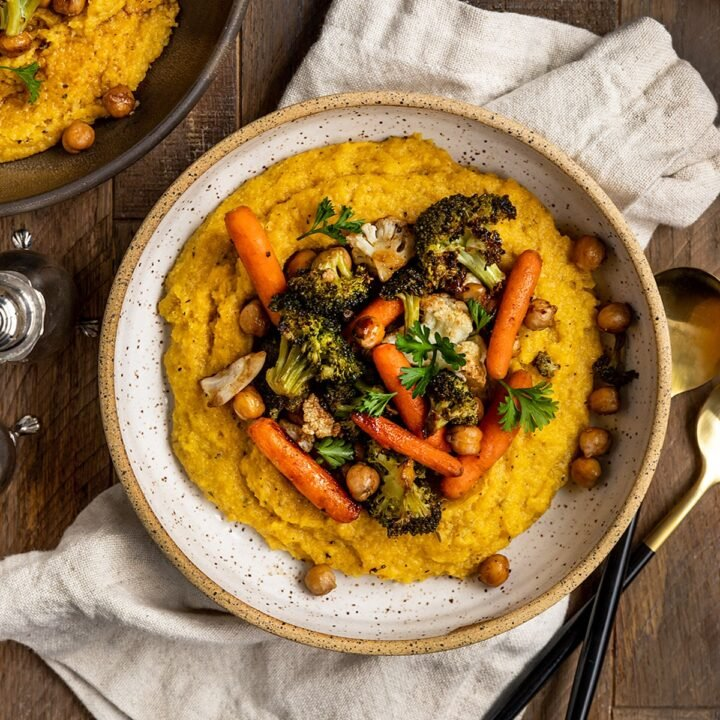 a bowl of polenta with roasted carrots, broccoli, cauliflower, and chickpeas on top