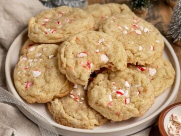 plate of cookies filled with chopped up candy cane pieces on a plate, one with a bite taken out