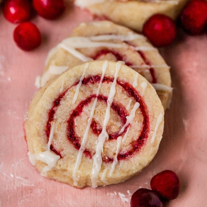close up shot of cranberry swirl pinwheel cookies with glaze on top