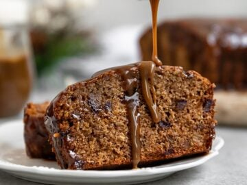 slice of a date loaf cake getting drizzle of caramel sauce on top