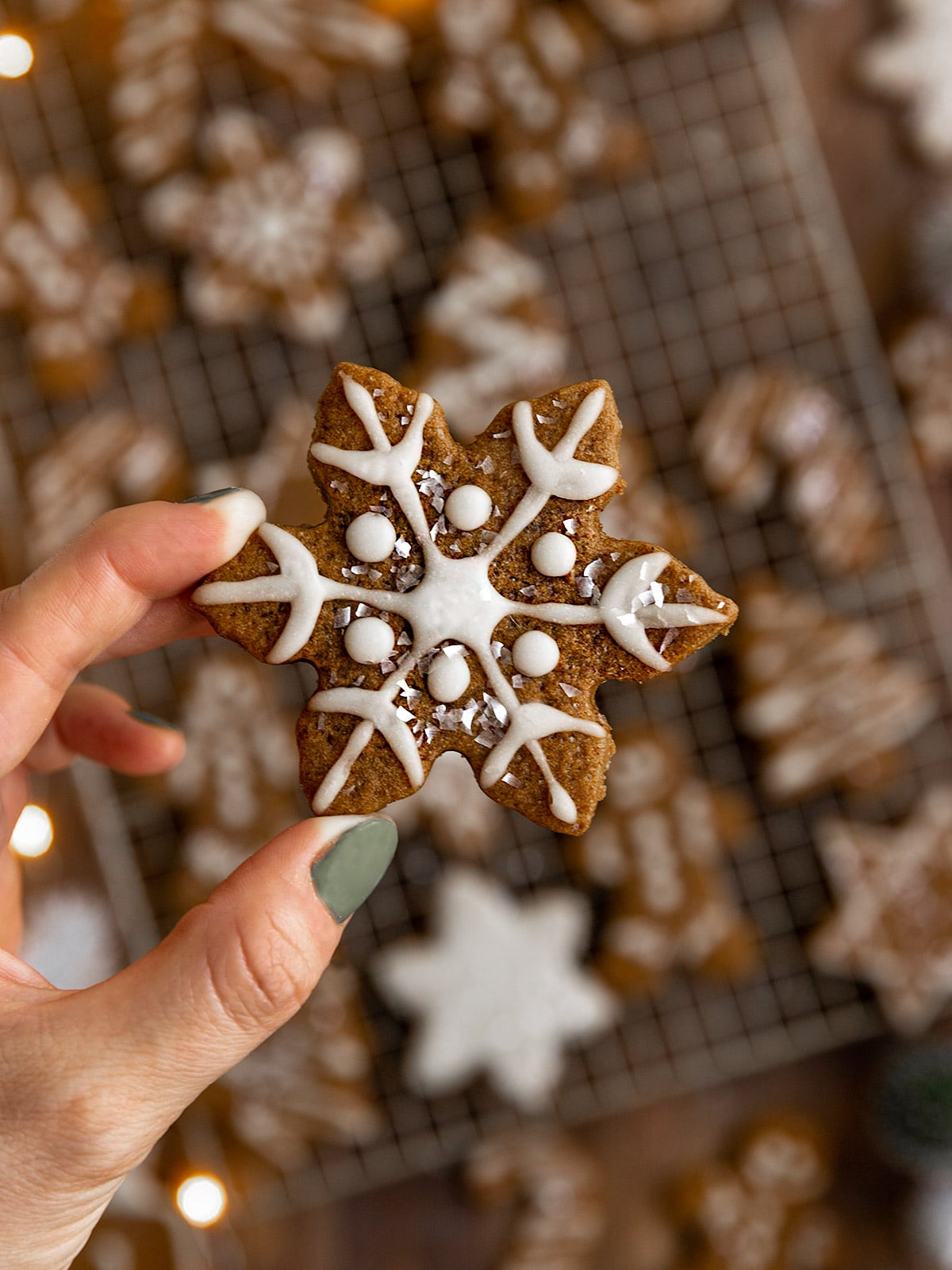 hand holding a decorated snowflake gingerbread cookie