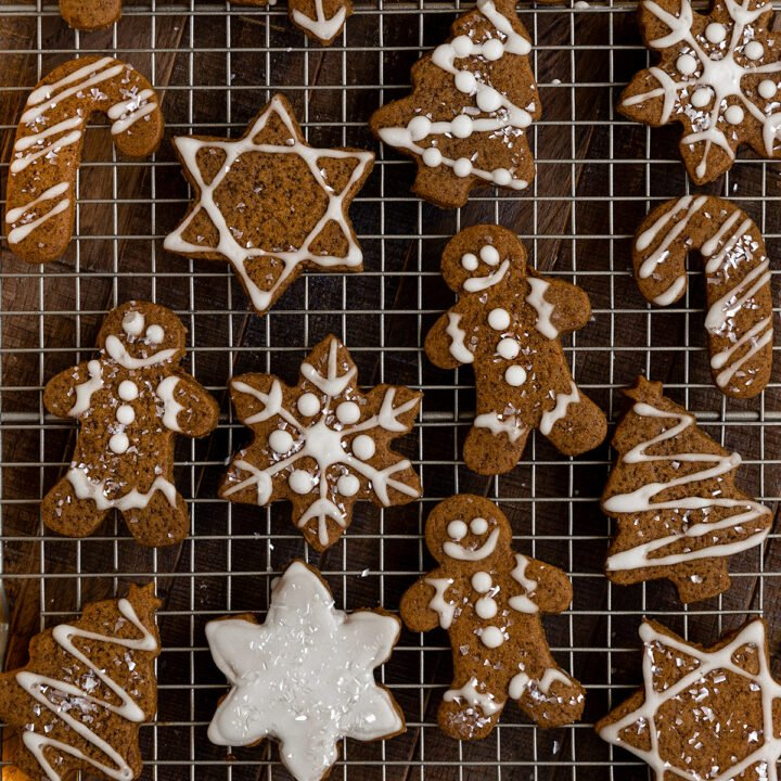 wire rack full of gingerbread cookies in shapes of gingerbread men, stars, snowflakes, christmas trees, dreidels