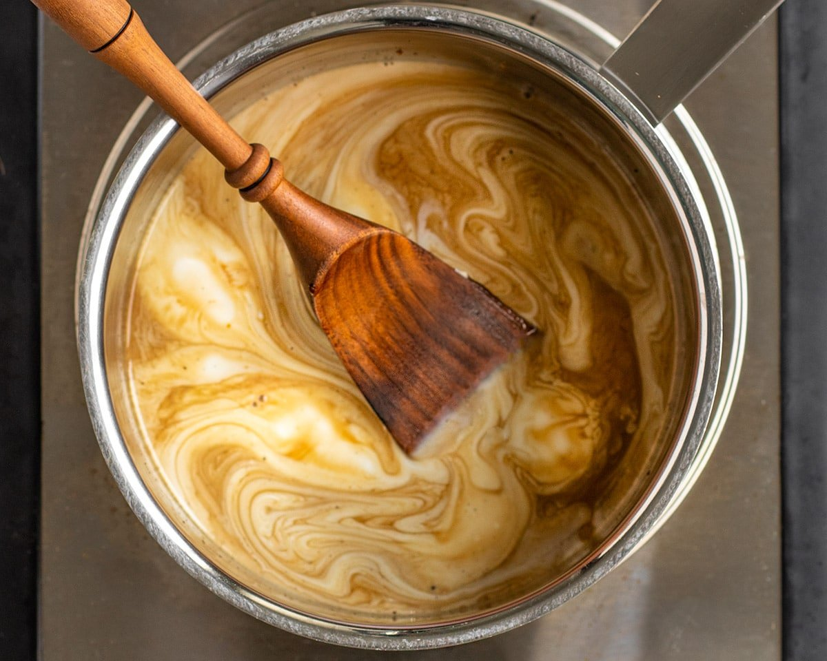 salted caramel ingredients swirled into saucepan