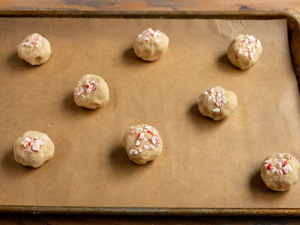 tray of cookie dough balls with peppermint candy pieces on top