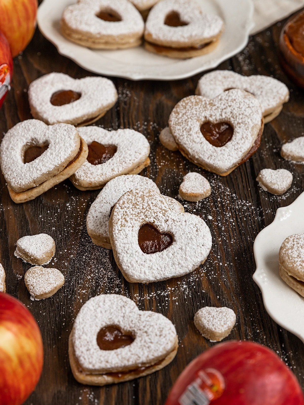 shot of heart shaped apple butter linzer cookies surrounded by apples