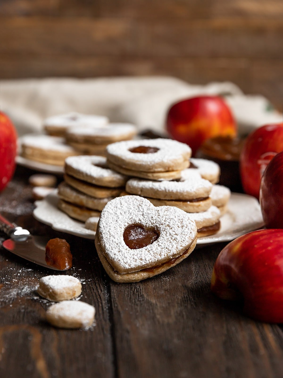 heart shaped linzer cookie leaning against plate on stacked cookies