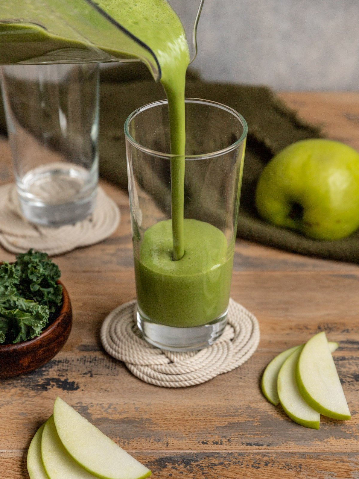 green smoothie being poured into a tall glass