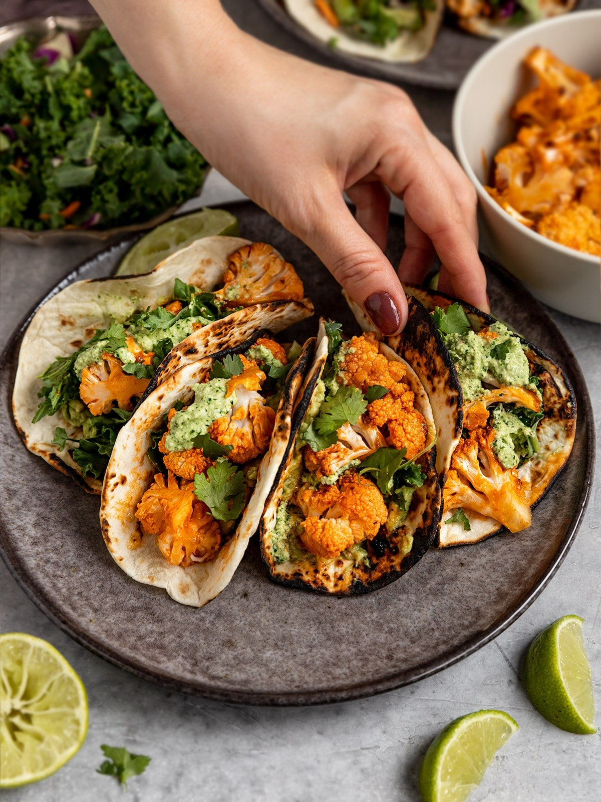 hand grabbing taco from a plate of buffalo cauliflower tacos