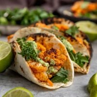 close up shot of taco filled with buffalo cauliflower, kale, carrots, and a green sauce on top