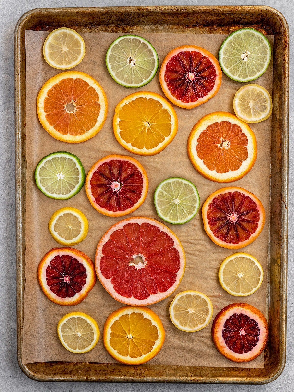 slices of oranges, lemons, limes, grapefruit, and blood oranges on a baking tray