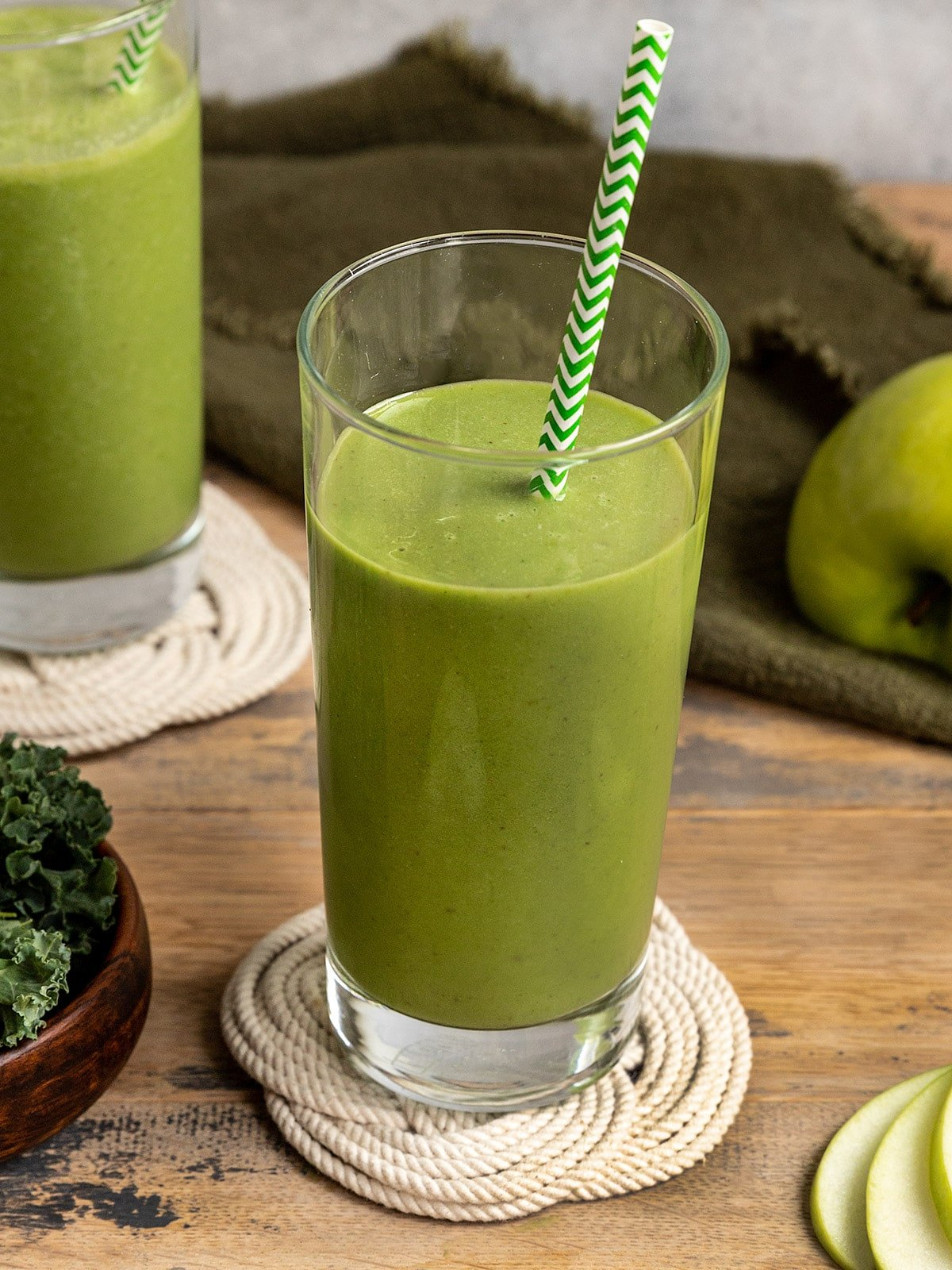 green smoothie in a glass with a green and white striped paper straw
