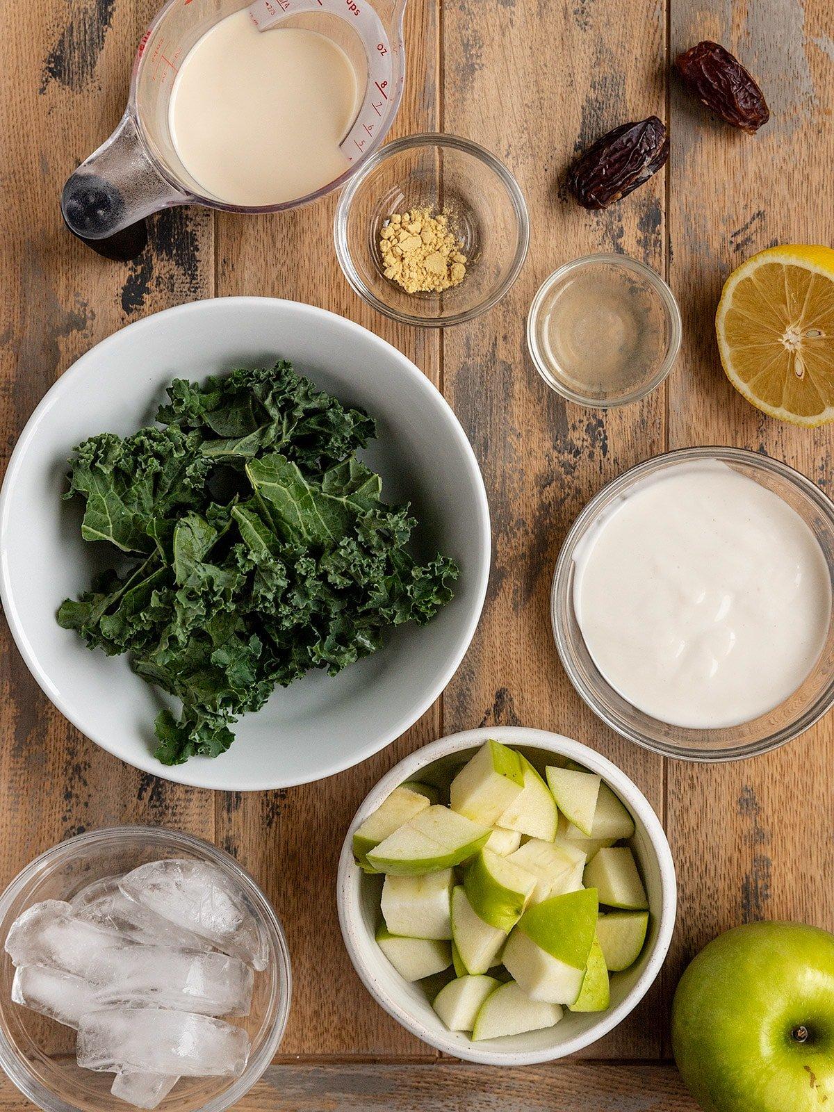 overhead shot of smoothie ingredients in bowls including kale, green apple, yogurt, lemon juice, oat milk, medjool dates, ice, and ginger