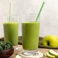 two green smoothies in glasses with green apple slices and kale surrounding them