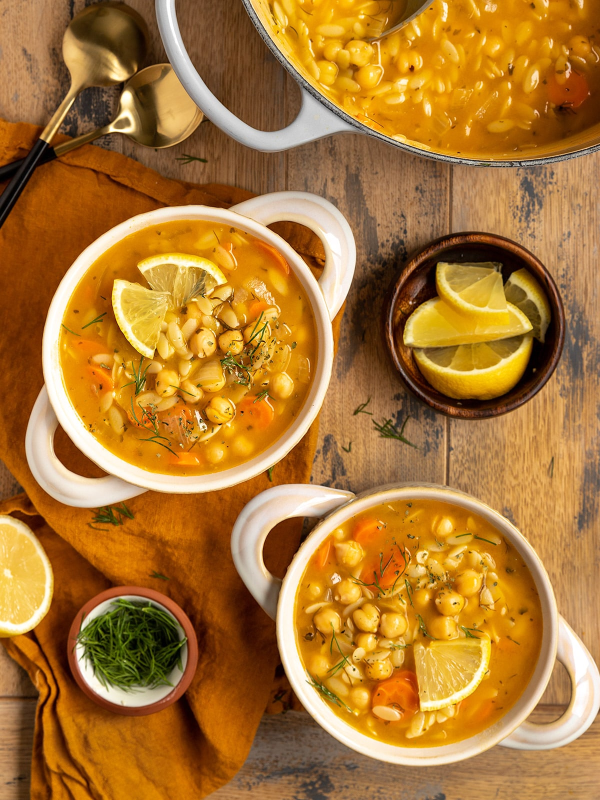 two bowls of soup filled with lemon, chickpeas, orzo, dill, and carrots
