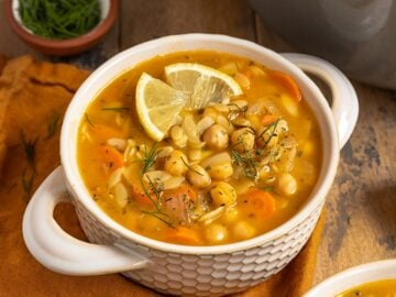 a bowl of soup with chickpeas, carrots, orzo, dill, and fresh lemon wedges on top