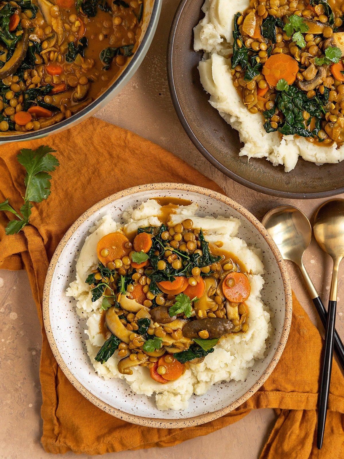 two bowls of lentil stew alongside a pot of lentil stew