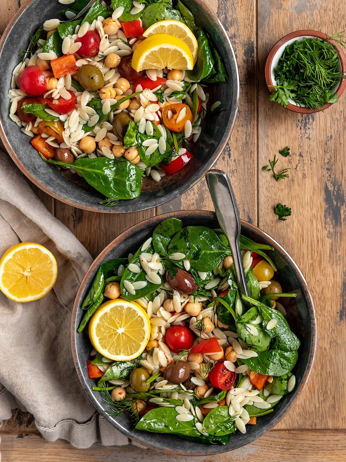 two bowls of salad filled with spinach, orzo, tomatoes, red pepper, fresh dill, parsley, chickpeas, and olives with a lemon slices on top