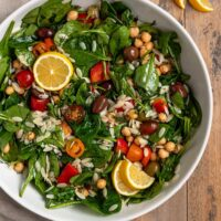 big bowl of salad filled with spinach, orzo, chickpeas, tomatoes, olives, fresh dill, parsley, red pepper, and lemon slices
