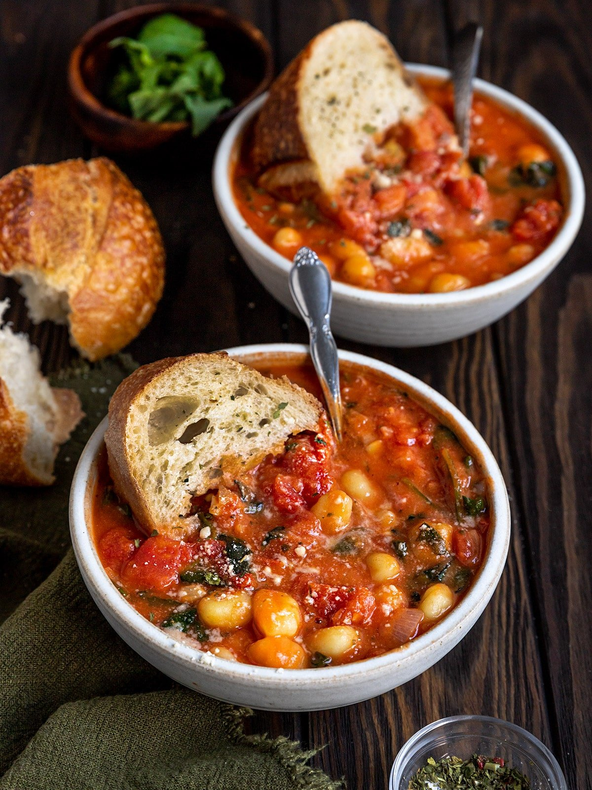two bowls of soup filled with tomato, gnocchi, spinach, basil, and a piece of sourdough bread