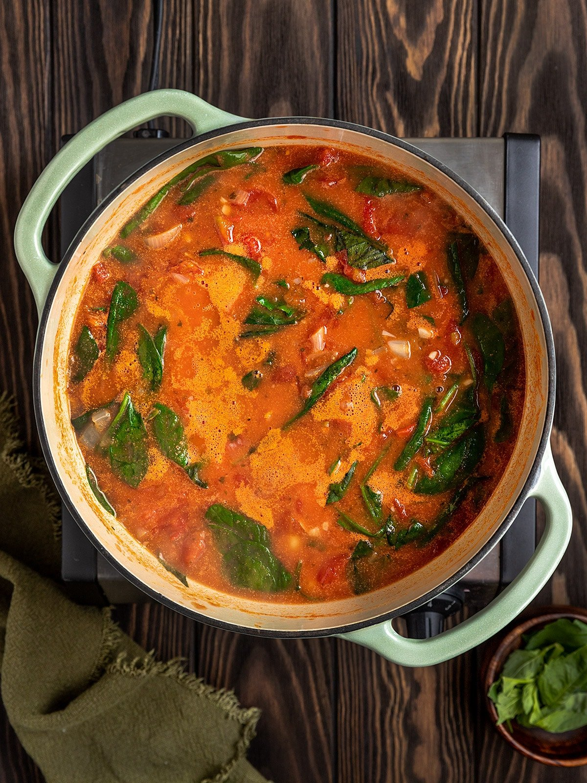 dutch oven filled with a tomato, spinach, basil, gnocchi soup