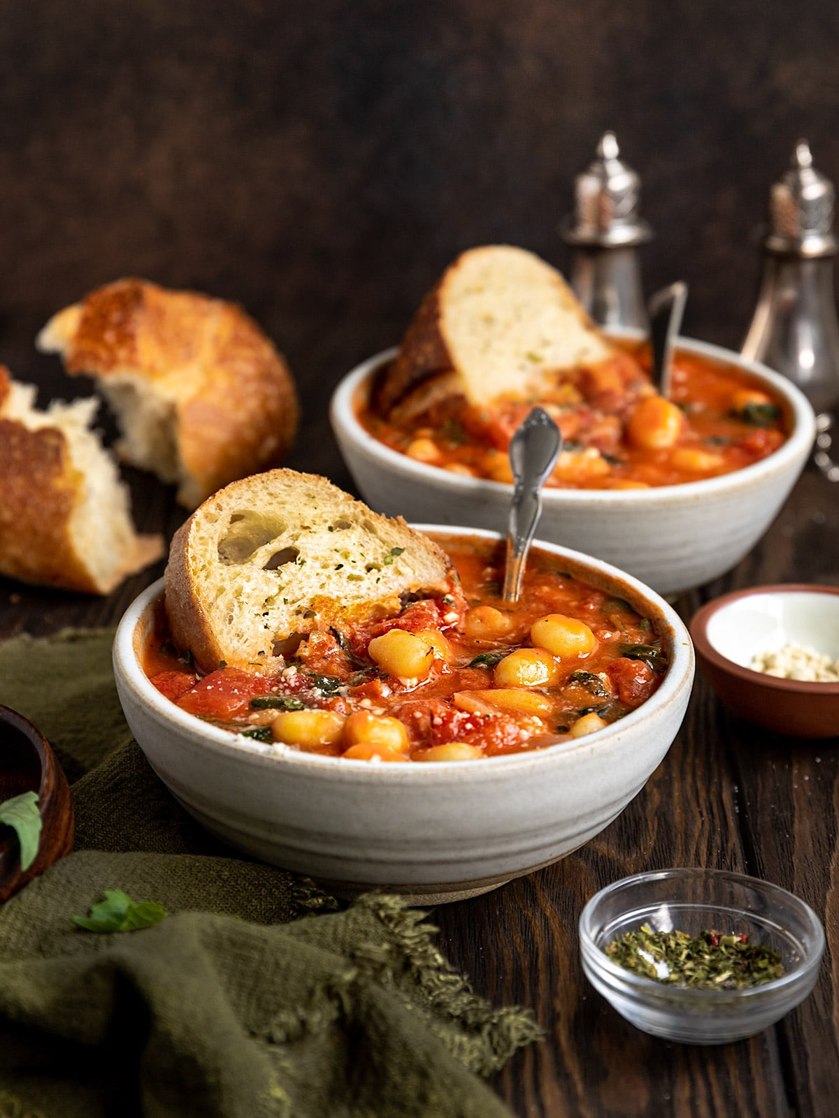 two bowls of tomato gnocchi soup with slices of sourdough bread on a wood table