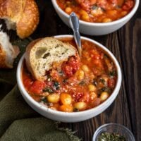 a bowl of soup filled with tomato, gnocchi, spinach, basil, and a piece of sourdough bread