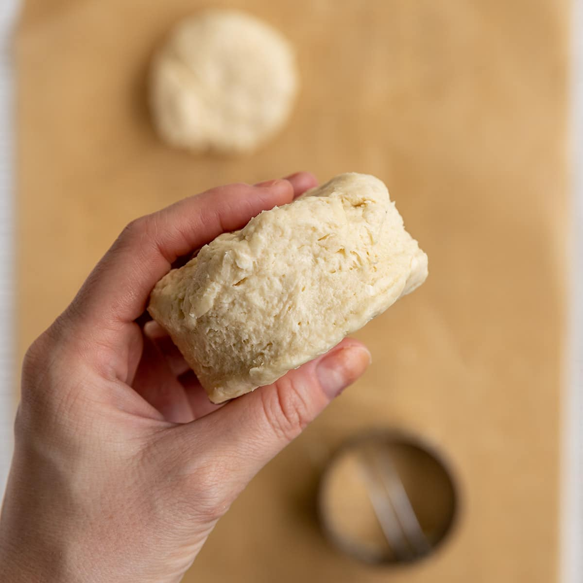 hand holding up an uncooked circle biscuit