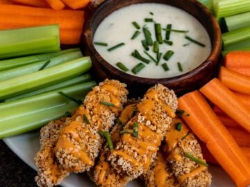 a plate filled with tempeh covered in buffalo sauce, carrots, celery, and a bowl of ranch dip
