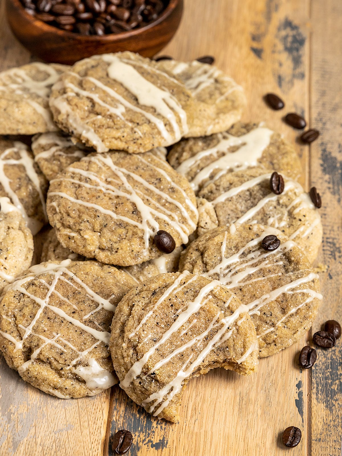 pile of espresso cookies with glaze on top surrounded by coffee beans and one cookie missing a bite