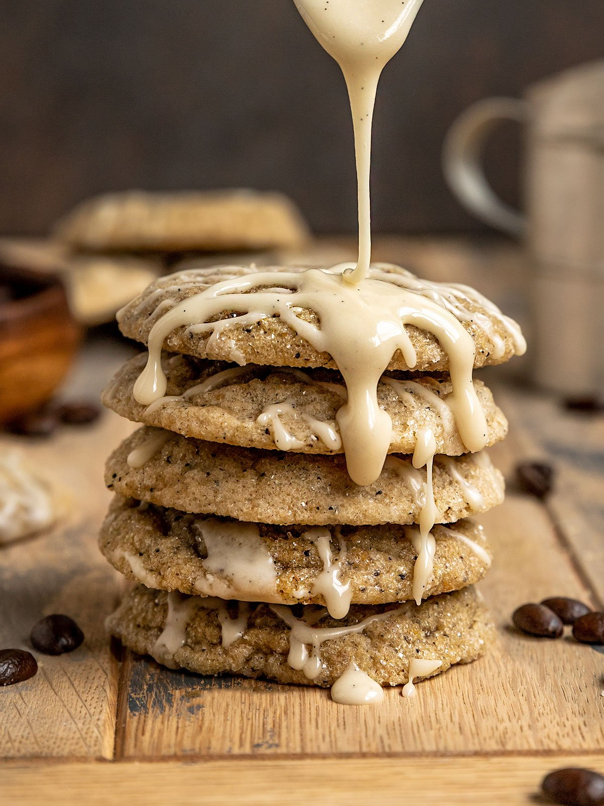 spoonful of vanilla bean glaze being drizzled onto a stack of coffee cookies