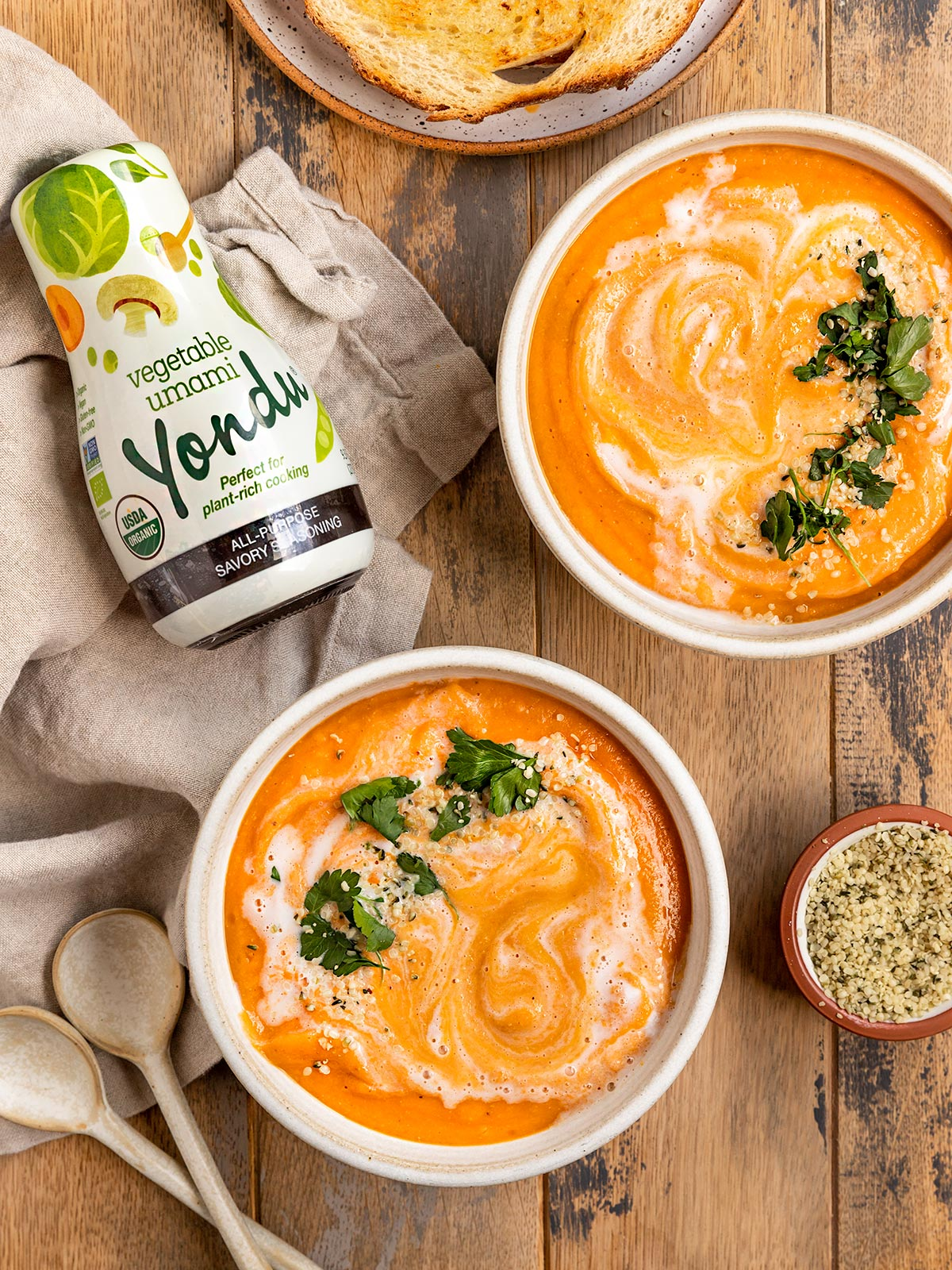 two bowls of carrot lentil ginger soup with cilantro and hemp seed garnish beside a bottle of yondu sauce