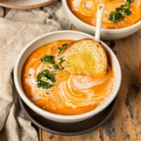 two bowls of carrot lentil soup with a slice of bread, cilantro, hemp seeds, and a swirl of coconut cream on top