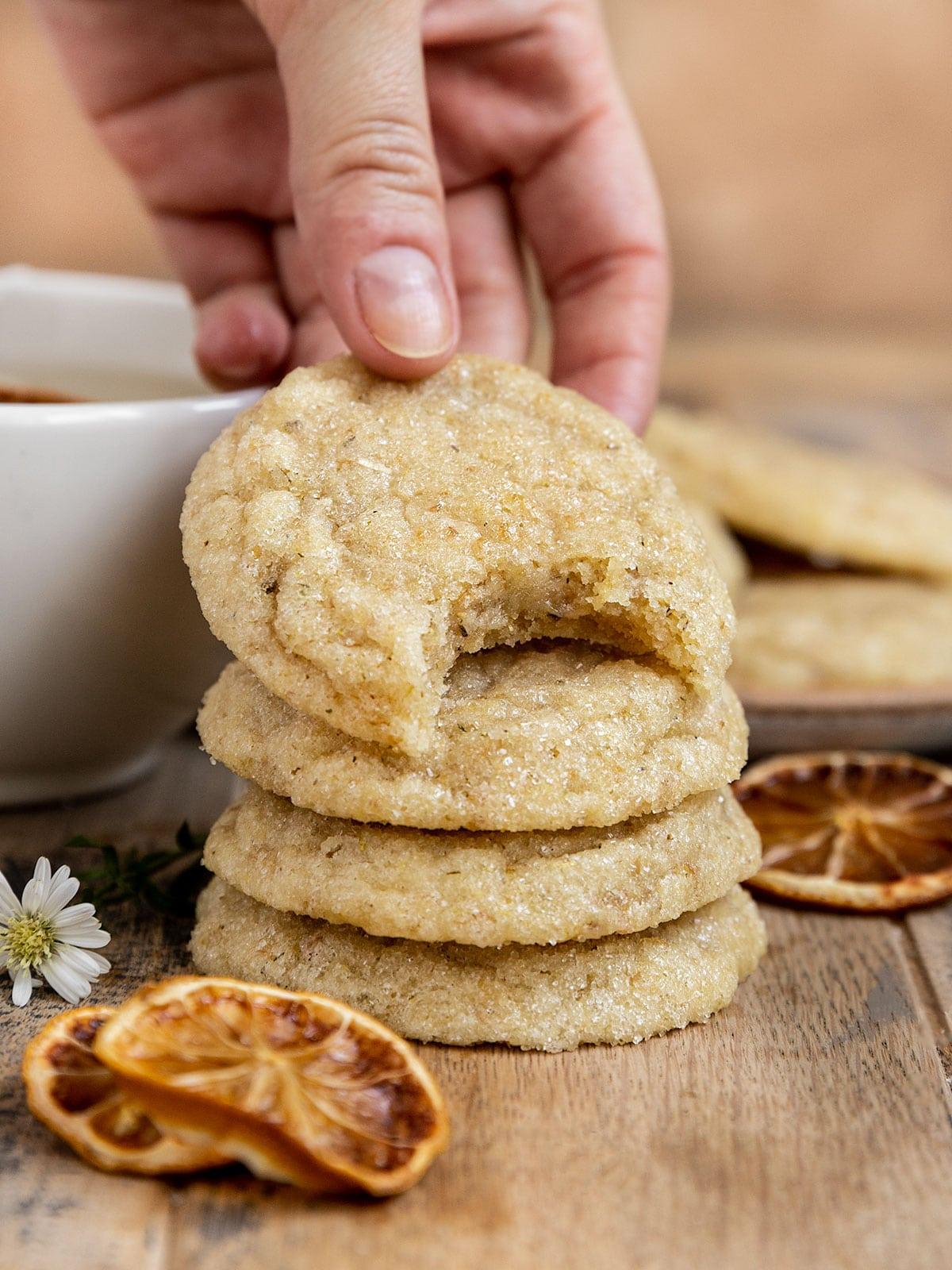 hand lifting a bitten chamomile cookie from a stack of cookies