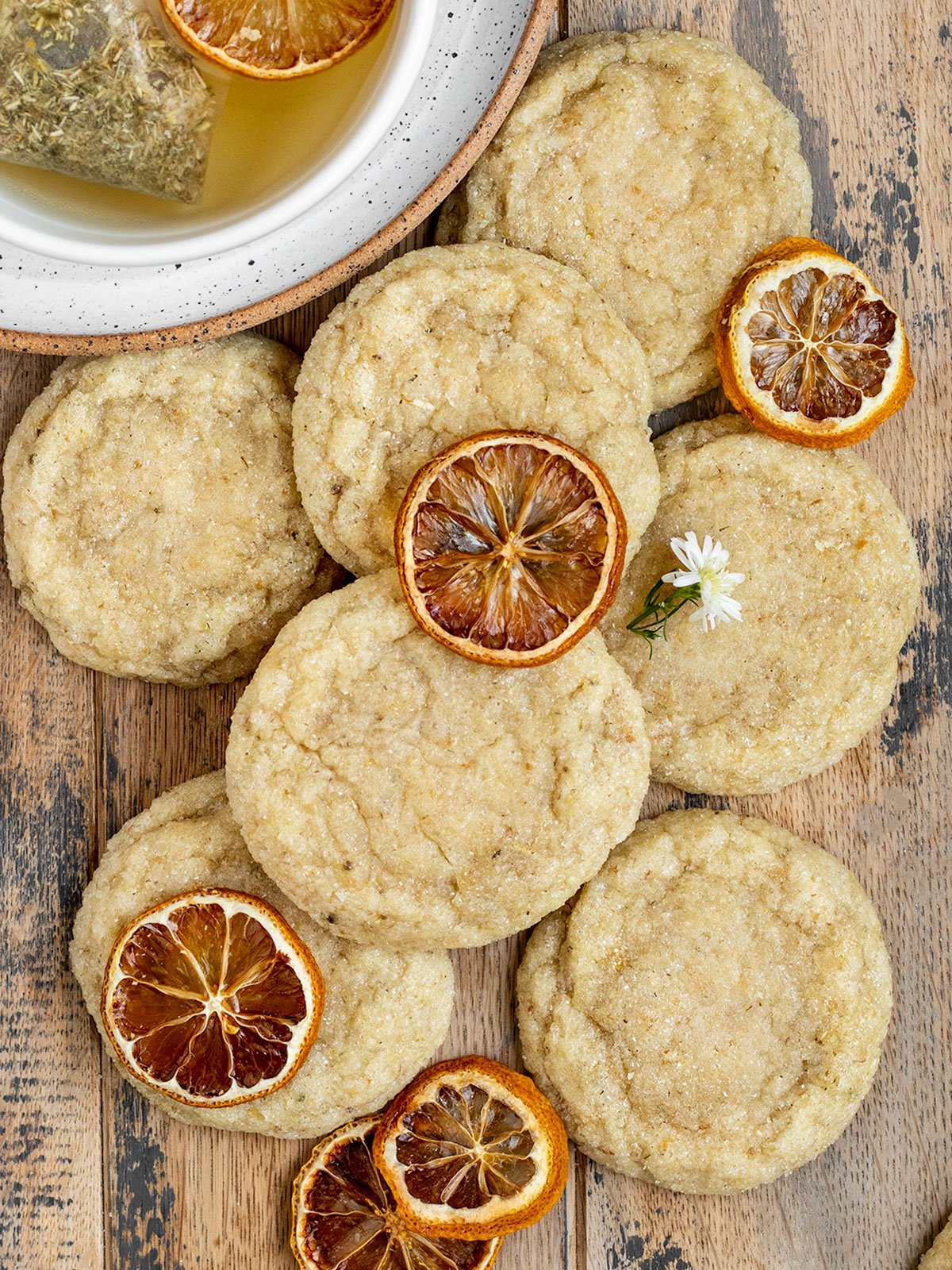 overhead shot of stacks of chamomile cookies with dried lemon slices and chamomile flowers