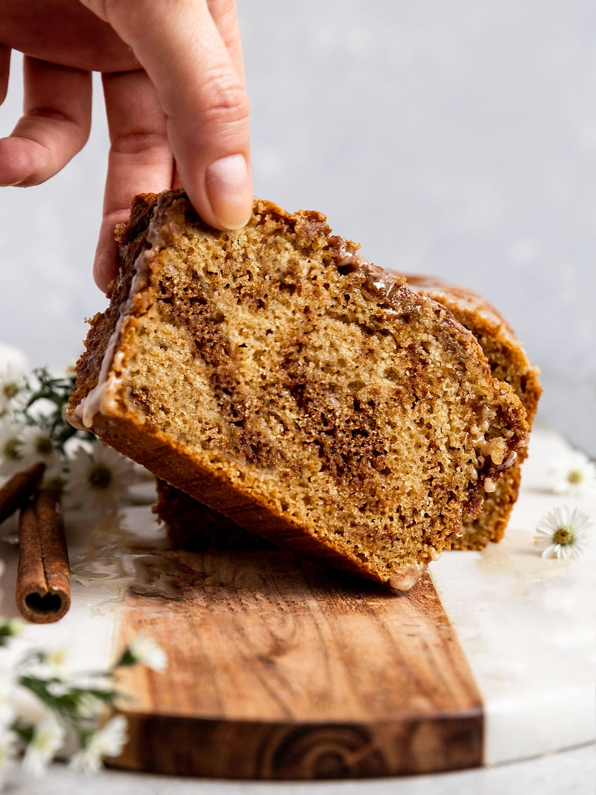 hand lifting up a slice of cinnamon swirl bread from a loaf